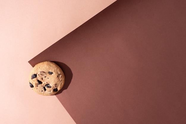 Jeden plik cookie z kawałkami czekolady na tle brązowego papieru w słońcu, widok z góry