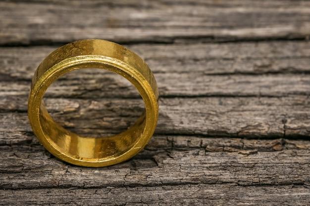 Jeden pojedynczy złoty pierścień na drewnianym stole z miejscem na kopię