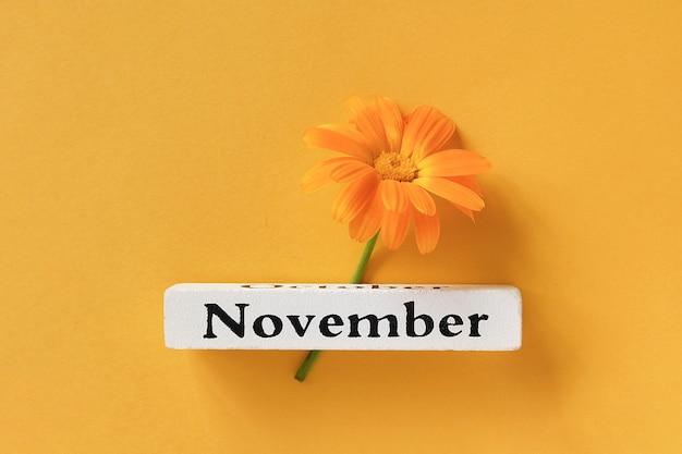 Jeden pomarańczowy kwiat nagietka i kalendarz jesień miesiąc listopad na żółtym tle.