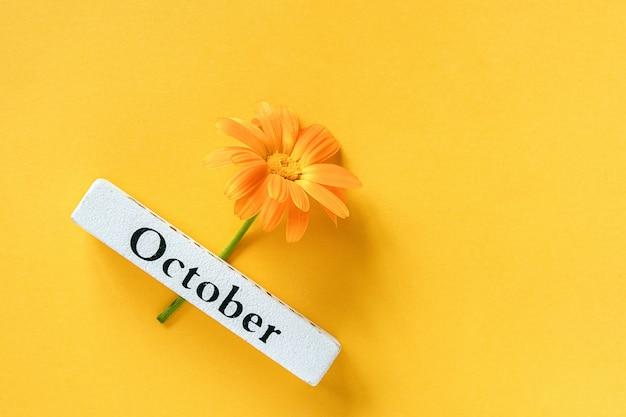 Jeden pomarańczowy kwiat nagietka i kalendarz jesień miesiąc październik na żółtym tle.