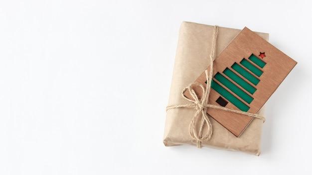 Jeden prezent w papierze pakowym z kartką z życzeniami z widokiem z góry na zielone choinki