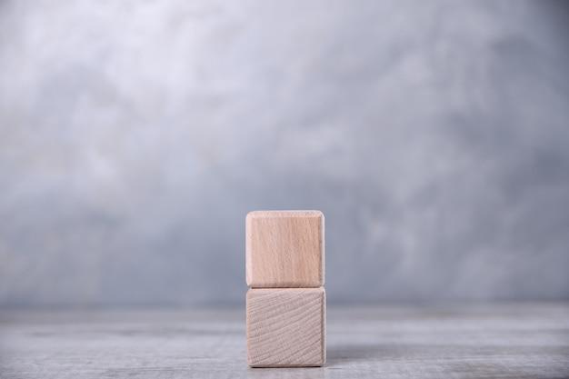 Jeden pusty drewniany sześcian na stole.