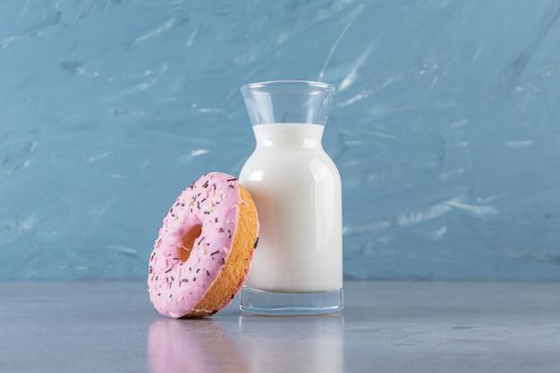 Jeden różowy pączek z posypką i szklany dzbanek świeżego mleka.
