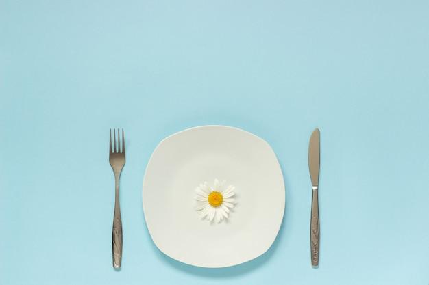 Jeden rumianek kwiat na talerzu, nóż widelec sztućce. koncepcja wegetariańska, zdrowe odżywianie, dieta lub anoreksja