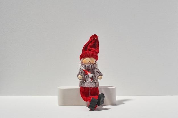 Jeden samotny elf boże narodzenie siedzi na białym tle. minimalna świąteczna koncepcja samotności