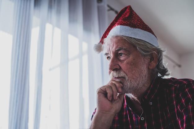 Jeden samotny i smutny starszy dojrzały mężczyzna siedzący na kanapie w domu świętujący boże narodzenie sam na sam z kimkolwiek - zdenerwowany dorosły czuje się źle