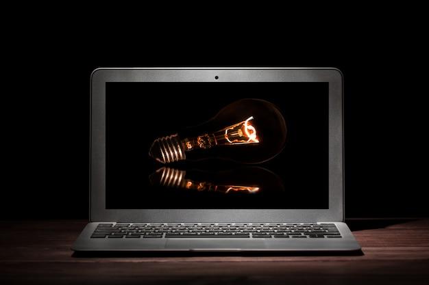 Jeden srebrny nowoczesny laptop ze świecącą żarówką na drewnianym stole w ciemnym pokoju na czarnej powierzchni.