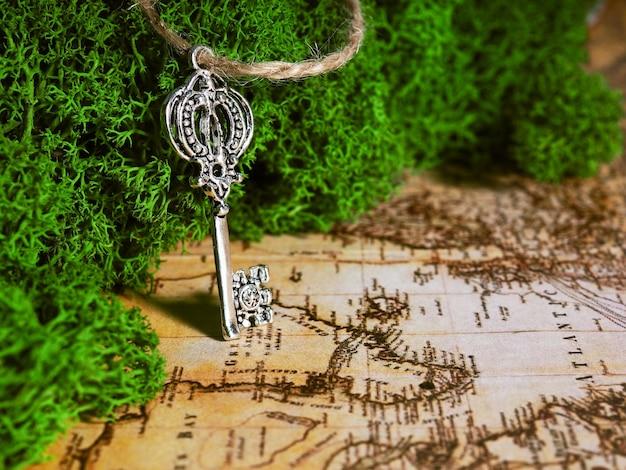 Jeden stary klucz leży na mchu na tle starej mapy, klucz do skarbu, podróży i przygody.