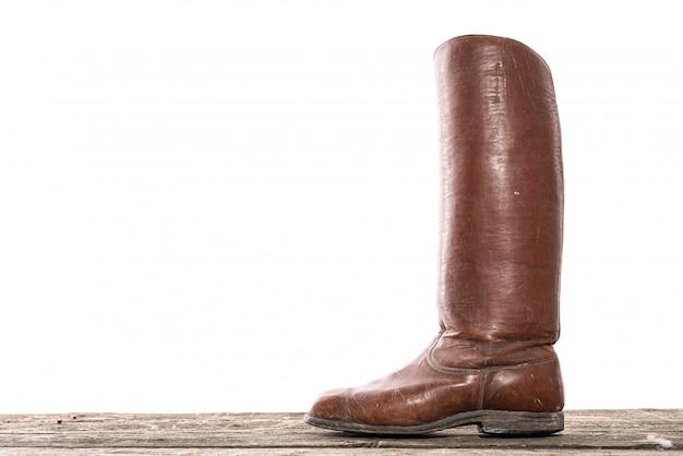 Jeden stary skórzany ręcznie robiony wysoki but na drewnianej podłodze na białym tle