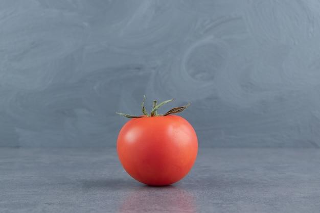 Jeden świeży czerwony pomidor na marmurowej powierzchni