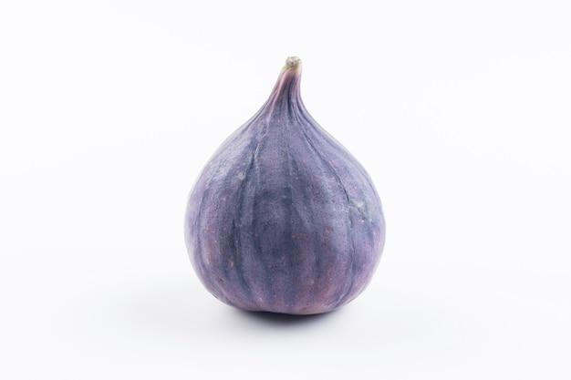 Jeden świeży fioletowy uncut raw fig samodzielnie na białym tle