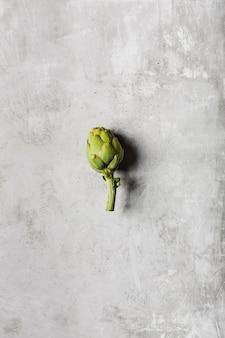 Jeden świeży karczoch na jasnoszarym stole. egzotyczne warzywo dla zdrowego odżywiania i diety