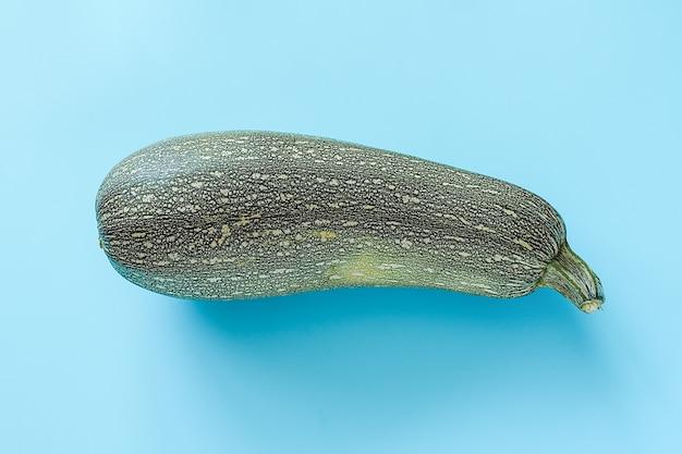 Jeden świeży zielony zucchini kabaczek na błękitnym tle z kopii przestrzenią.