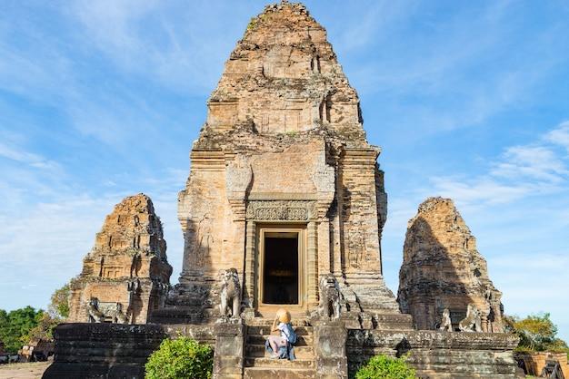 Jeden turysta odwiedzający ruiny angkor wśród dżungli, kompleks świątynny angkor wat, cel podróży kambodża. kobieta z tradycyjnym kapeluszem, widok z tyłu.
