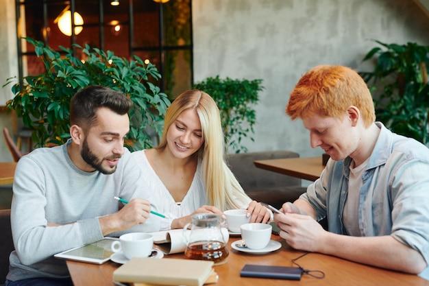 Jeden z bystrych facetów wskazujący na notatki w notatniku, omawiając wykład ze swoją dziewczyną w kawiarni po zajęciach