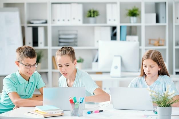 Jeden z bystrych uczniów, który pokazuje swojemu koledze z klasy zaciekawioną stronę internetową, na której mogą zdobyć informacje do swojego szkolnego projektu