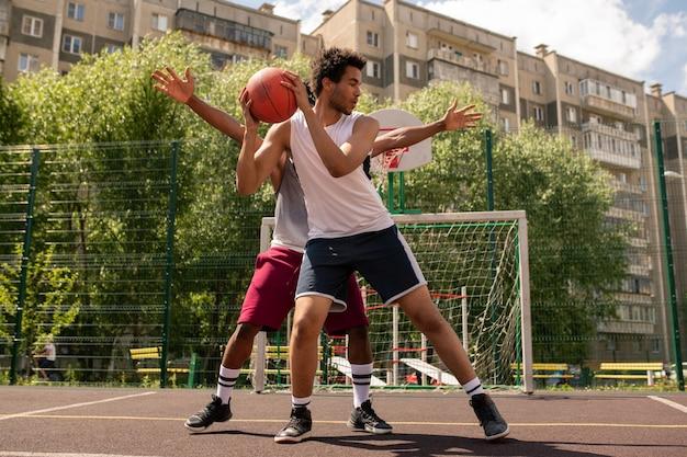 Jeden z koszykarzy z piłką, który stara się nie pozwolić rywalowi zabrać jej podczas gry na świeżym powietrzu