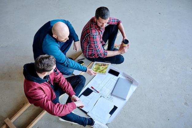 Jeden z młodych budowniczych pokazujący swoim kolegom zewnętrzną stronę gotowego domu na touchpadzie podczas dyskusji na temat materiałów wyposażenia na spotkaniu