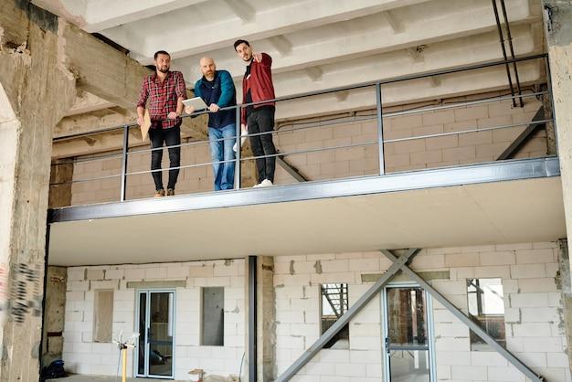 Jeden z trzech młodych architektów wskazujący na narożnik niedokończonego budynku podczas dyskusji o nowych materiałach na spotkaniu start-upowym