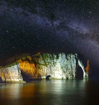 Jeden z trzech słynnych białych klifów znanych jako falaise de aval. etretat, francja. scena nocna z rozgwieżdżoną drogą mleczną w oświetleniu nieba i skał