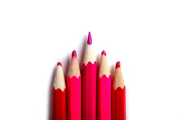 Jeden zaostrzony ołówek wyróżnia się od tępych. łatwo być pięknym, jeśli nic nie robisz. czerwoni ołówki na bielu.