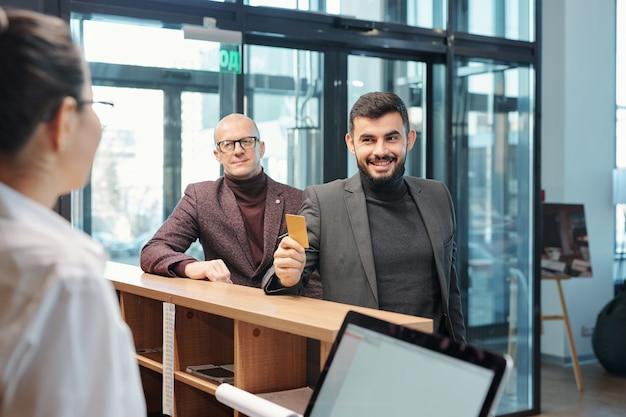 Jeden ze współczesnych biznesmenów, pokazujący recepcjonistce hotelową kartę plastikową przy zamawianiu noclegu
