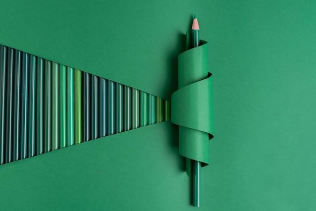 Jeden zielony ołówek w zwiniętym papierze na zielonym tle z zielonymi ołówkami.