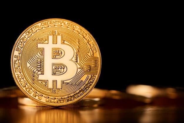 Jeden złoty bitcoin na krawędzi pokazany na tle innych kryptowalut wprowadzający przyszły trend wirtualnych pieniędzy.