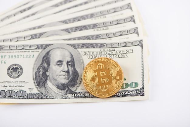 Jeden złoty bitcoin nakładający się stos banknotów stu dolarów