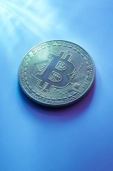 Jeden złoty bitcoin wyizolowany na niebieskim tle z bliska z kopią przestrzeni
