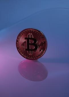 Jeden złoty bitcoin wyizolowany na różowym fioletowym tle z bliska z kopią miejsca