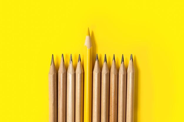 Jeden żółty ołówek wyróżniający się z serii szarych ołówków.