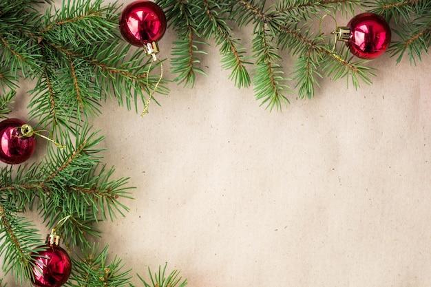 Jedlinowe gałąź dekorować z czerwonymi boże narodzenie piłkami jak granicę na nieociosanej wakacyjnej tło ramie z kopii przestrzenią