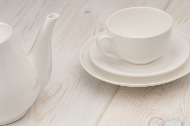 Jedna biała filiżanka i spodek oraz czajnik na starej drewnianej desce