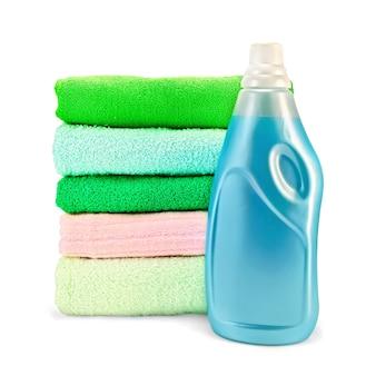 Jedna butelka niebieskiego płynu do płukania tkanin, stos ręczników na białym tle
