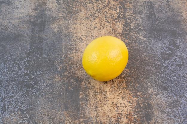 Jedna cała cytryna na kamiennej powierzchni