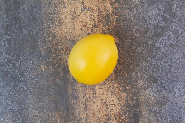 Jedna cała cytryna na marmurowej powierzchni