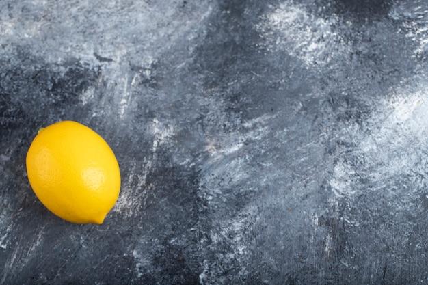 Jedna cała cytryna umieszczona na kamiennej powierzchni