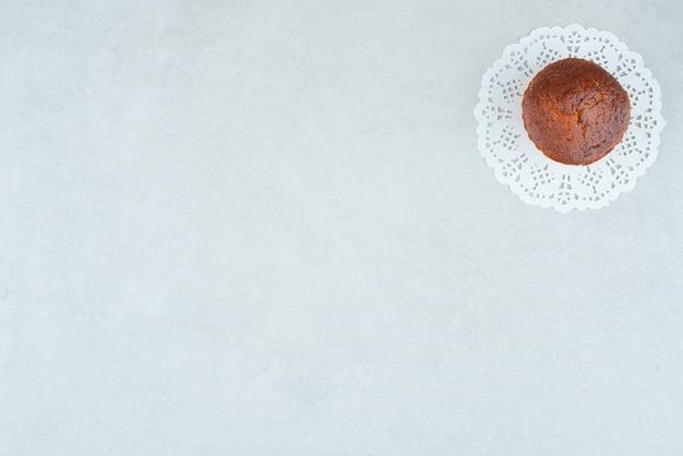 Jedna cała pyszna słodka babeczka na białym stole.