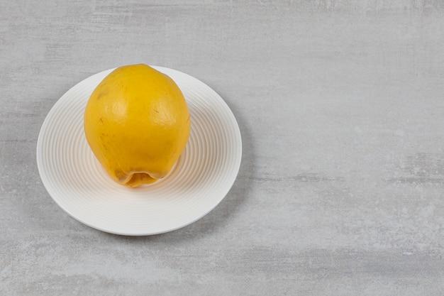 Jedna cytryna na talerzu na marmurowej powierzchni