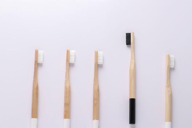 Jedna czarna szczoteczka do zębów eco odlatująca od innych białych szczoteczek do zębów na tle białej ściany. wyjątkowa, myśl odmienna, indywidualna i wyróżniająca się z tłumu koncepcja orientacja pozioma
