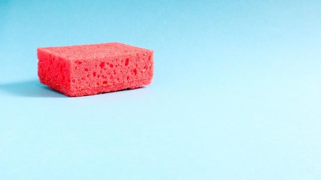 Jedna czerwona gąbka na niebieskim tle służy do zmywania i usuwania zabrudzeń używanych przez gospodynie domowe w życiu codziennym. wykonane są z porowatego materiału. oszczędność detergentu, co pozwala oszczędnie go używać.
