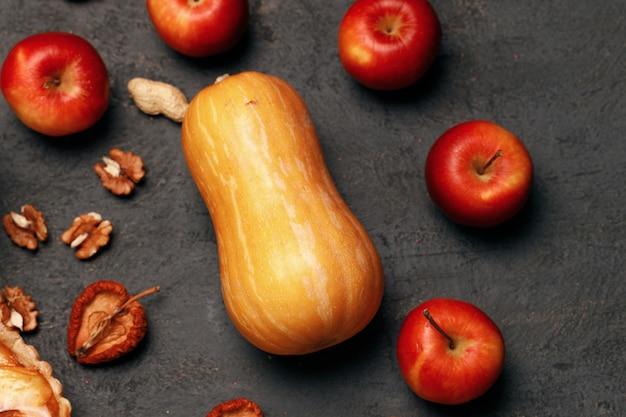 Jedna dynia i czerwone jabłka