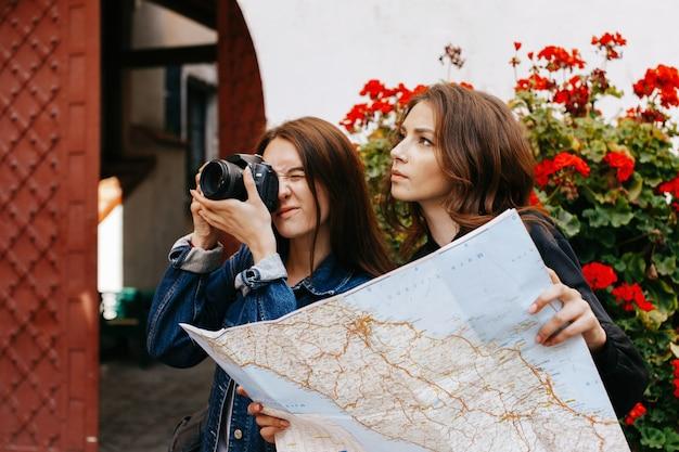 Jedna dziewczyna robi zdjęcie, podczas gdy inna patrzy na mapę turystyczną