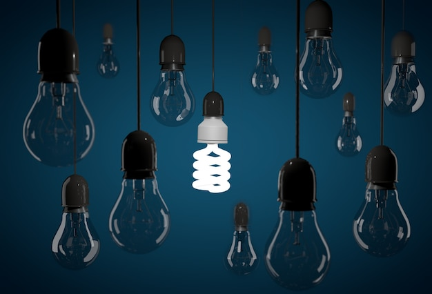 Jedna energooszczędna żarówka oświetlająca ciemną żarówkę wiszącą na przewodach na niebieskim tle