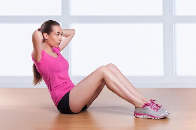 Jedna kobieta ćwiczy chrupiące ramiona treningu fitness za głową