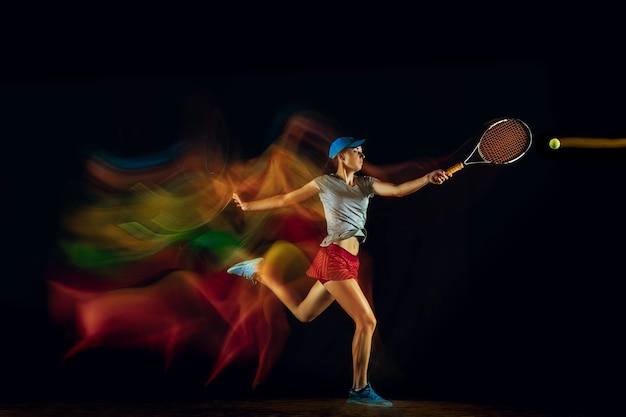 Jedna kobieta, grając w tenisa na białym tle na czarnej ścianie w świetle mieszanym i stobe