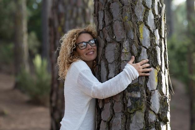 Jedna kobieta przytula z zamkniętymi oczami stare drzewo w lesie