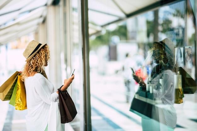Jedna kobieta samotna i odizolowana w centrum handlowym patrząca na szybę sklepu w mieście z telefonem w dłoni - modna kobieta chce coś kupić i z trzema torebkami na plecach