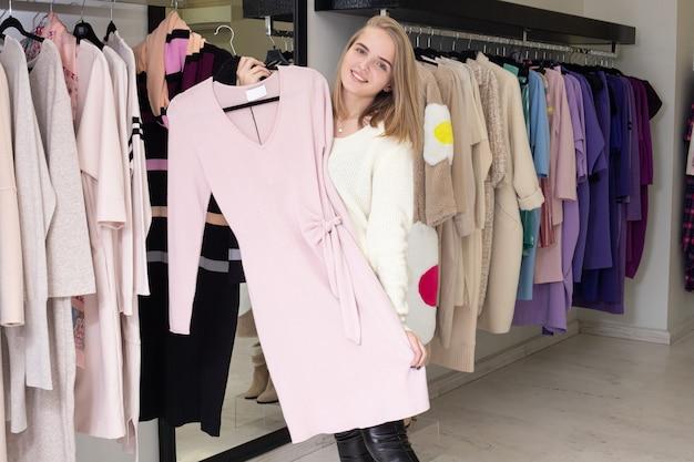 Jedna kobieta wybiera ubrania na wieszakach sklepowych